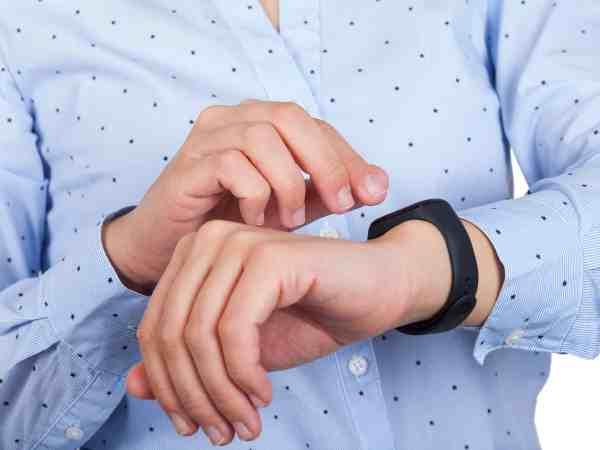 Na imagem há o peito e braços de um homem com uma pulseira inteligente e camisa azul de bolinhas.