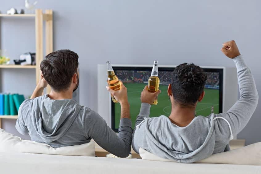 Imagem de dois rapazes assistindo a uma partida de futebol na televisão.