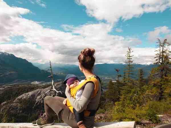 Mão sentada em topo de montanha apreciando a vista com bebê no canguru.