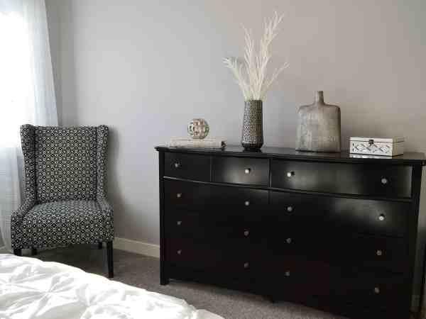 Imagem mostra uma cômoda preta em um quarto com poltrona ao lado.