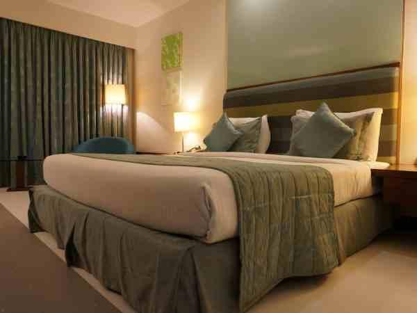 Na imagem está um quarto de casal com roupas de cama e decoração em tons de verde.