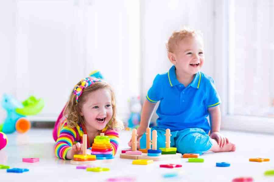 Na foto uma menina e um menino no chão brincando com alguns brinquedos de madeira.