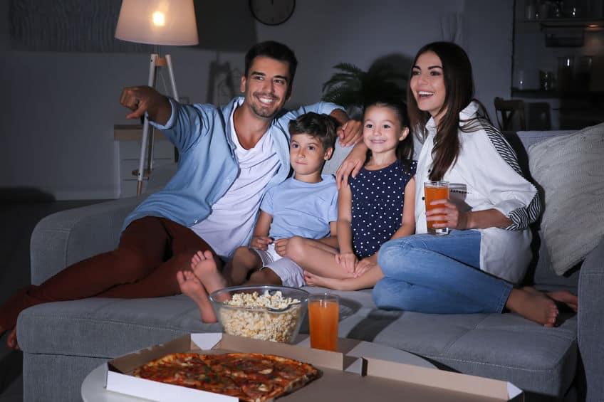 Imagem de uma família assistindo a um filme na televisão.
