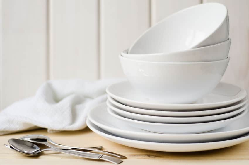 Imagem de jogo de prato branco sobre mesa com talheres e guardanapo ao lado.