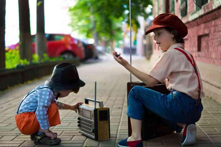 Duas crianças estão em uma calçada. A menor está agachada na frente de um rádio portátil pequeno. A outra, maior, está agachada com um rádio portátil maior. Ambas usam roupas que remetem a épocas antigas.