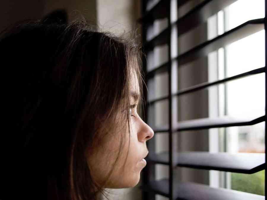 Imagem de criança olhando para fora através de uma persiana.