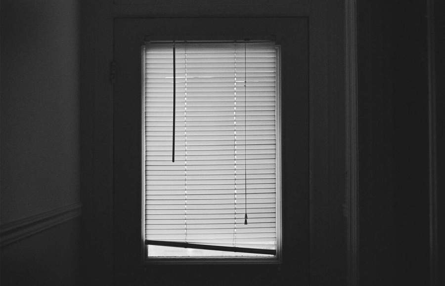 Imagem preto e branco de uma porta com persiana.