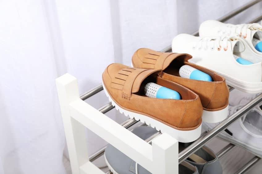 Imagem de sapatos em uma sapateira de prateleiras.
