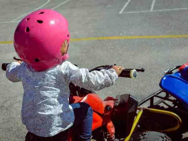 Criança de costas, de capacete e pilotando um quadriciclo infantil.