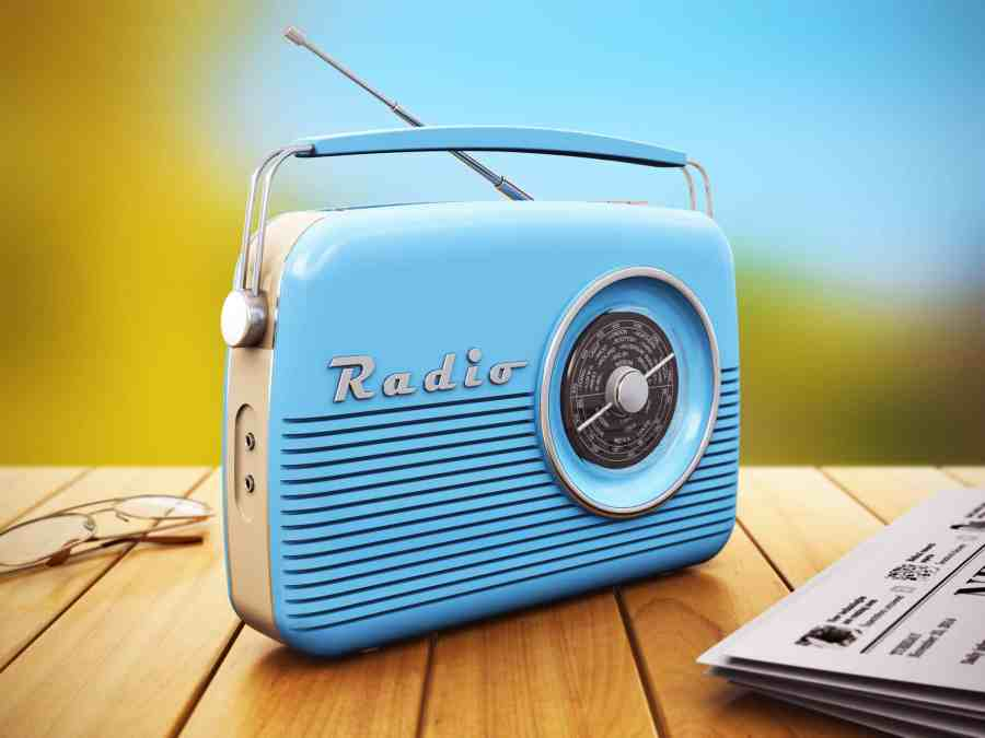 Rádio portátil azul sobre mesa de madeira ao lado de jornal