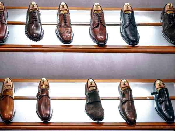 Foto de uma sapateira com vários sapatos sociais de diferentes cores e estilos.