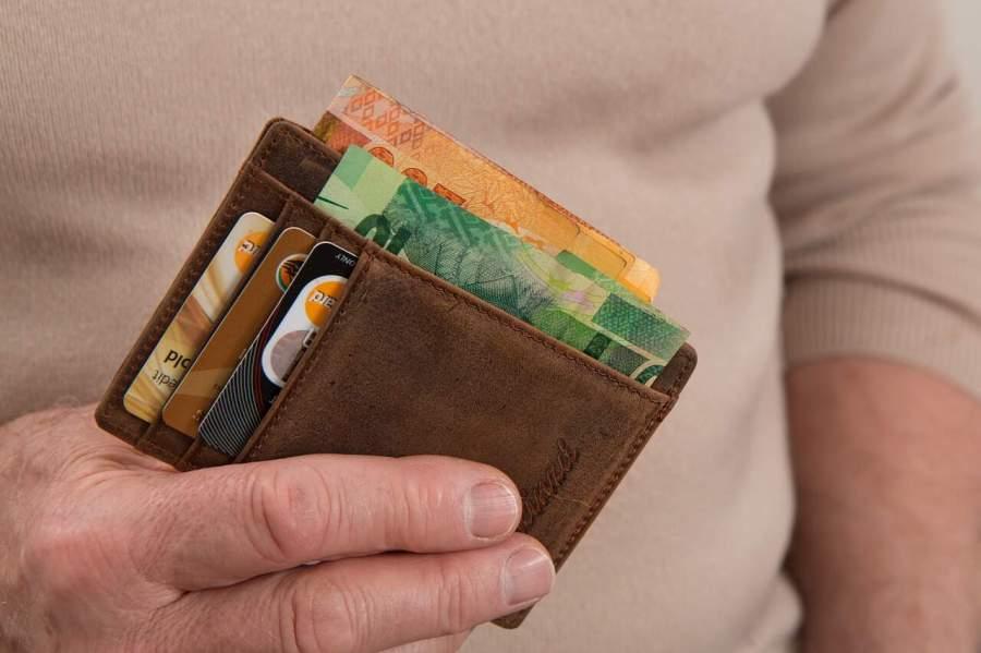 Imagem de pessoa segurando um porta documentos marrom com dinheiro e cartões de crédito.