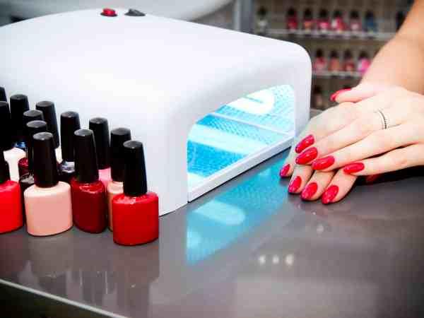 Foto de duas mãos femininas pintadas de vermelho, uma em cima da outra, ao lado de uma câmara de led para aplicação de gel e de esmaltes em tons de vermelho.