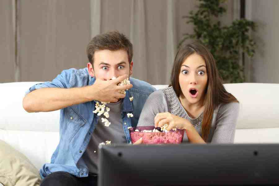 Na foto um casal comendo pipoca olhando assustados para uma televisão sentados em um sofá.