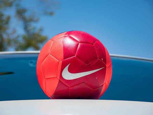 Imagem mostra uma bola da Nike, com o seu logo centralizado. Sua cor quente contrasta com o fundo azul.