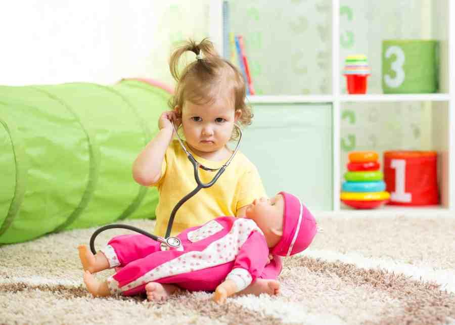 Bebê brincando de médico com boneca.