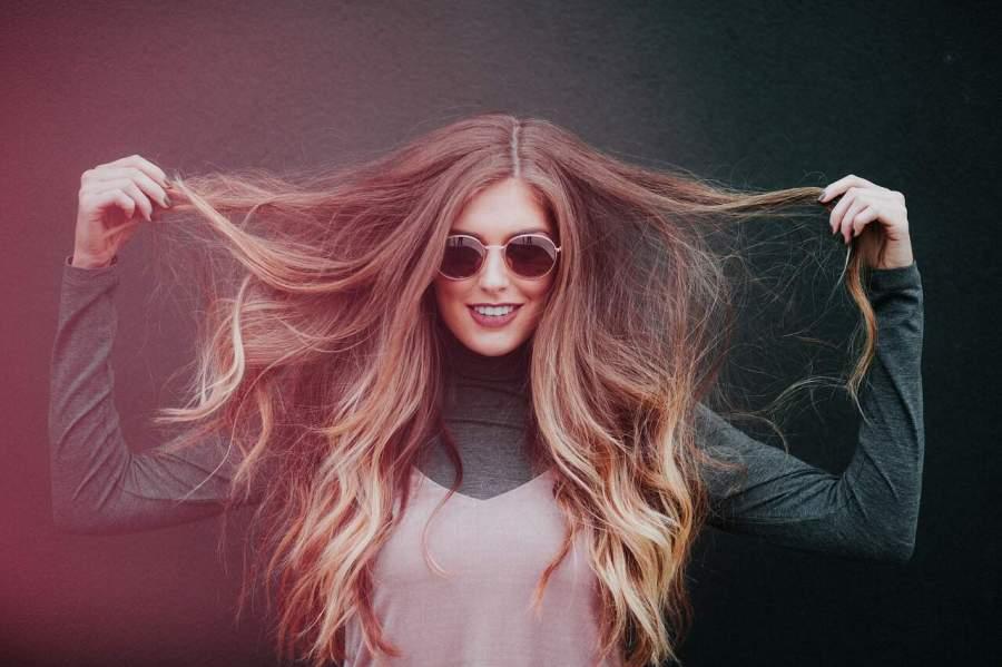 Imagem de uma mulher levantando algumas mechas de cabelo.