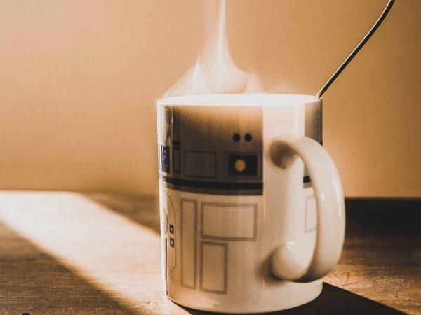 Imagem mostra uma caneca do R2-D2 em cima de uma mesa de madeira.