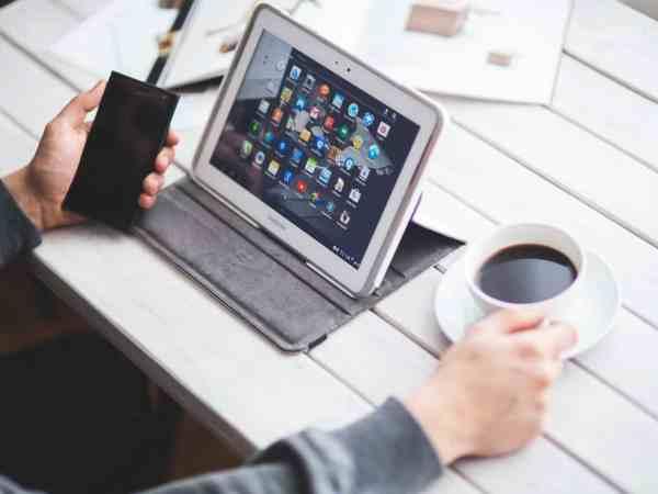 """Foto que mostra os braços de uma pessoa apoiado a uma mesa, com uma das mãos segurando um café e a outra um celular. Na sua frente, entre os dois objetos, um tablet acoplado em uma capa, apoiado na mesma para se manter """"em pé""""."""