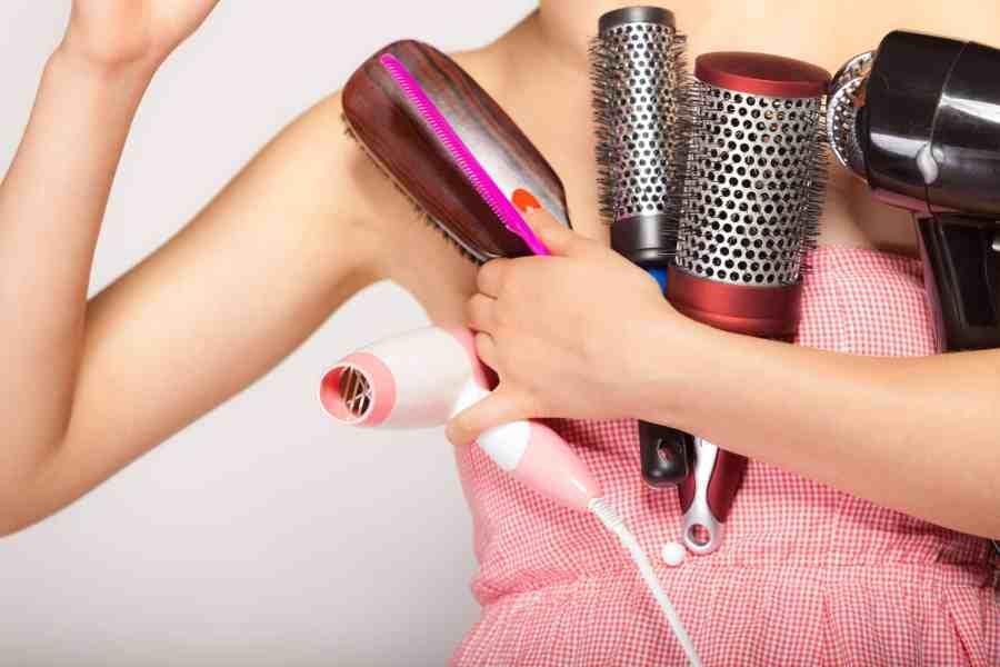 Foto de pessoa segurando escovas de cabelo e secador.