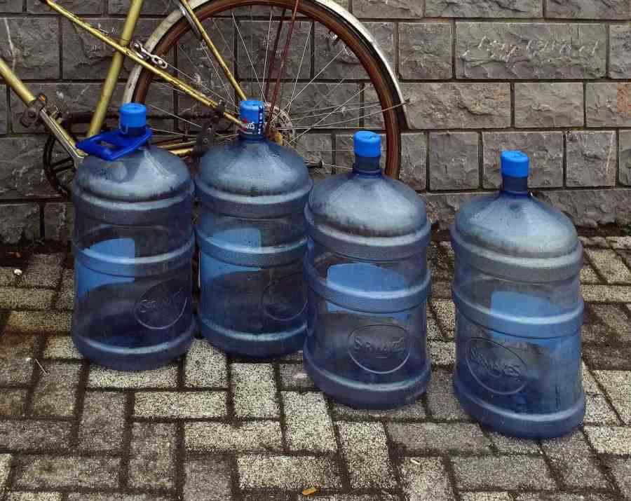 Quatro galões grandes de água mineral no chão com uma bicicleta atrás.