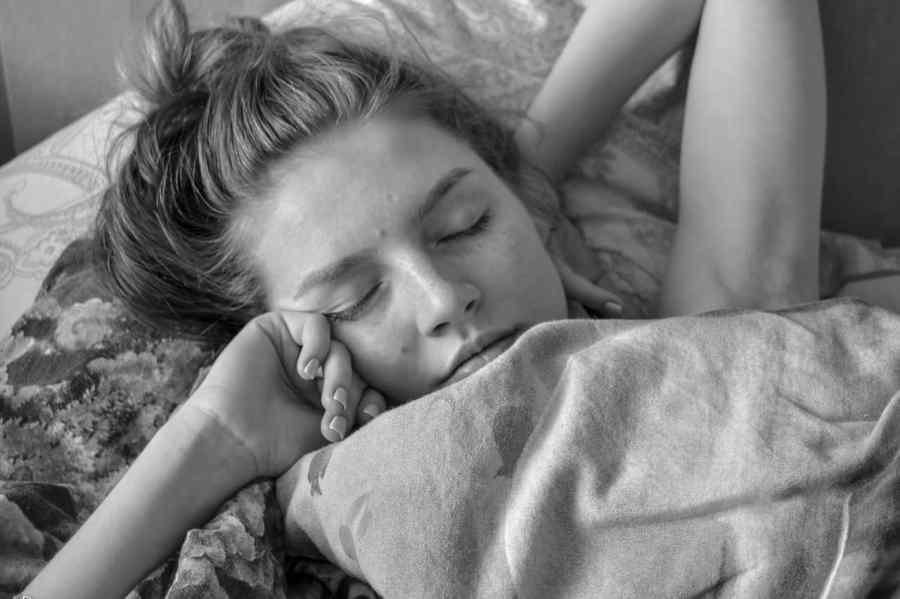 Uma mulher acordando na cama, ela está coberta por um edredom.
