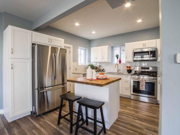 Na foto uma cozinha cinza, com armários brancos, uma ilha, uma geladeira french door e piso em madeira.