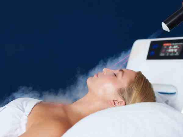 Na foto uma mulher deitada recebendo um tratamento com um vaporizador facial.