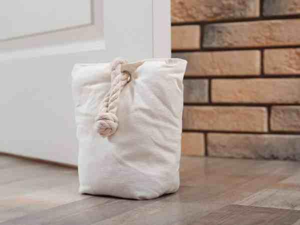 Peso de porta formato saco segurando porta branca.
