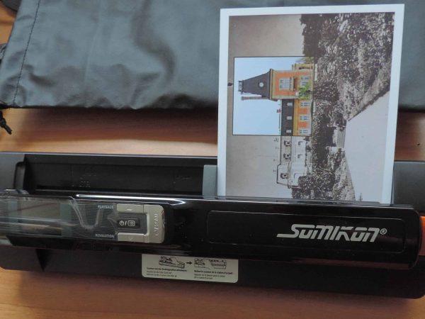 Imagem mostra um scanner portátil digitalizando uma foto.