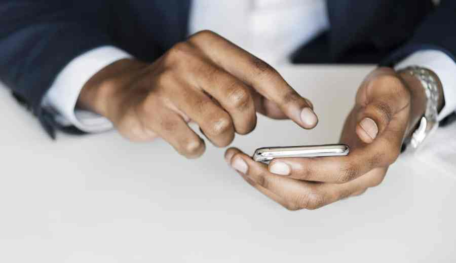 Mãos de um homem teclando no smartphone.