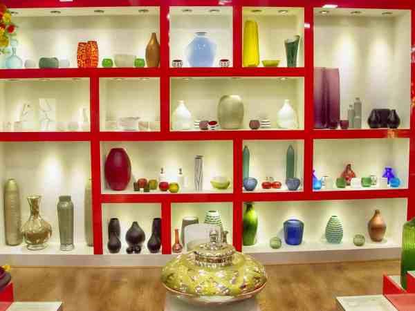 Parede divisória com grandes nichos e vários vasos decorativos de diferente formatos e cores.