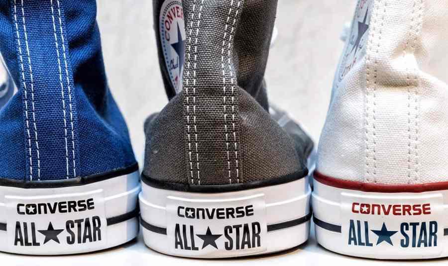 Na foto três tênis All Star de cano alto sendo um azul marinho, um cinza e um branco.