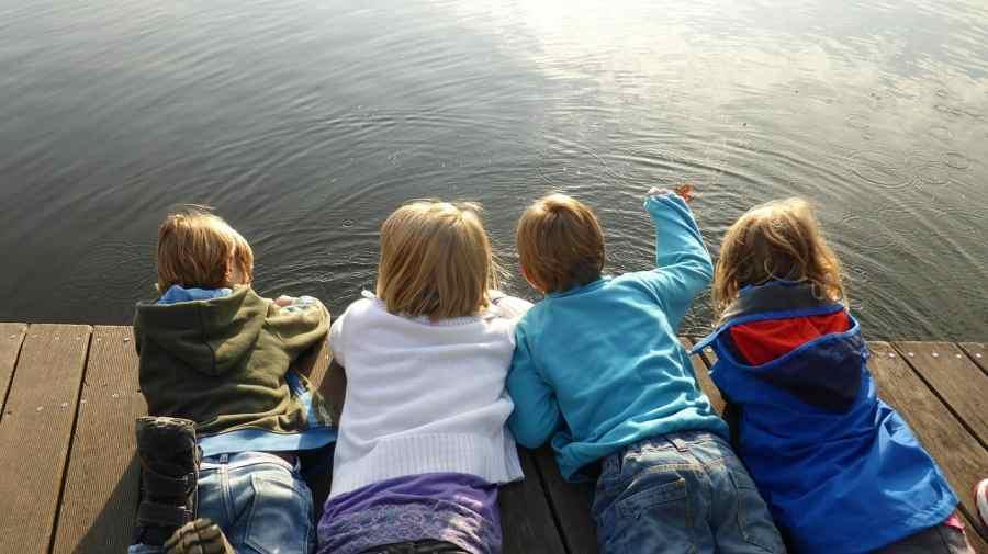 Quatro crianças deitadas de bruços sobre um píer de frente para a água.