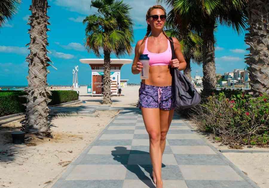 Imagem de uma mulher caminhando com uma coqueteleira nas mãos.