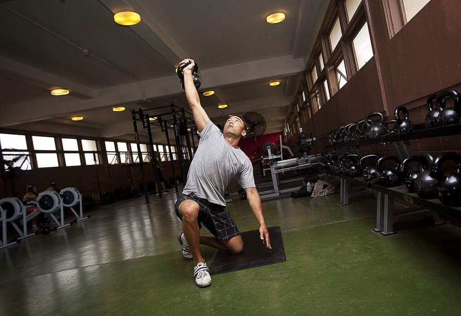 Homem levantando peso na academia.
