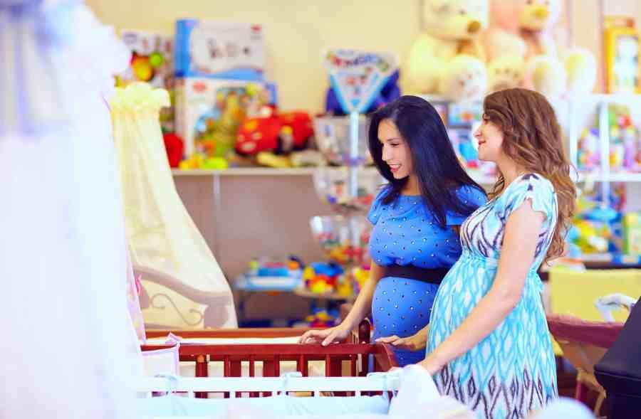Na foto duas mulheres grávidas em uma loja de itens para bebê.