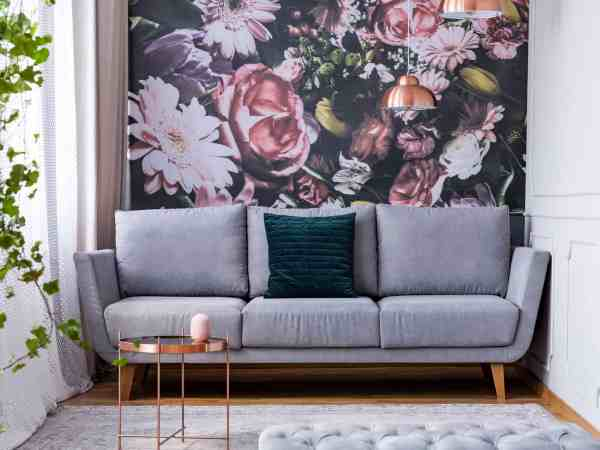 Copper table on carpet and green pillow on grey couch in flowers living room interior. Real photo