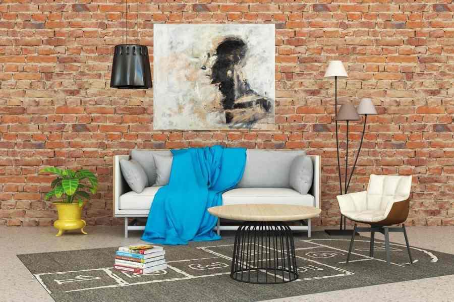 Sala com sofá, cadeira e mesa de centro, com papel de parede de tijolinho atrás.