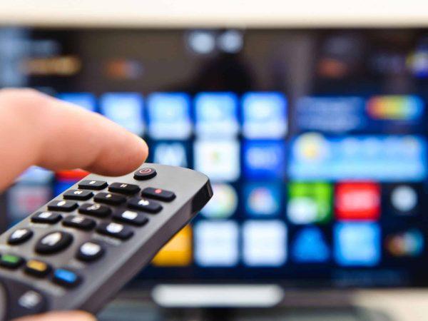 Foto com foco em uma mão segurando um controle remoto, que está apontado para uma smart tv, ao fundo.
