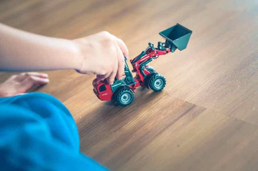 Na foto uma criança com um trator de brinquedo.