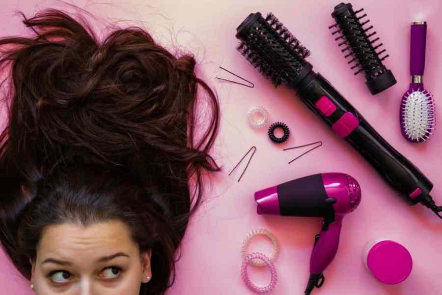Mulher ao lado de secador de cabelo, escovas, grampos e escova rotativa.
