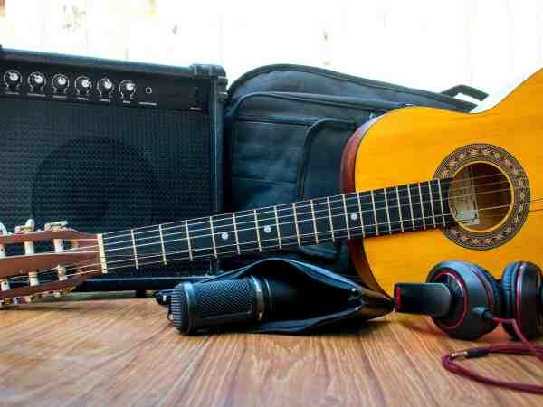 Uma capa para violão ao lado de um amplificador e atrás de um violão.