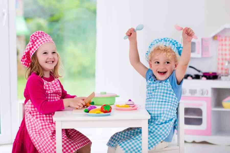 Menina e menino brincando de cozinhar.