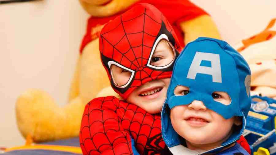 Na foto dois meninos fantasiados de super-heróis.