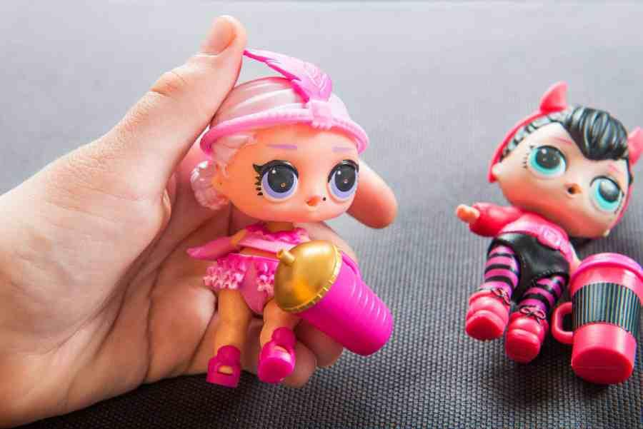 Mão segurando uma boneca LOL e outra boneca ao lado.