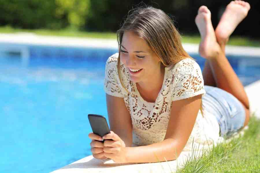 Imagem de uma jovem mexendo no celular na beira da piscina.