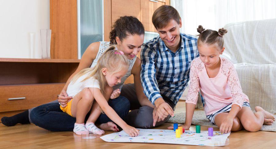 Família sentada no chão jogando.