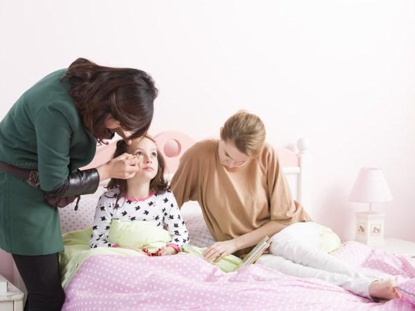 Adulta maquiando menina em cama.