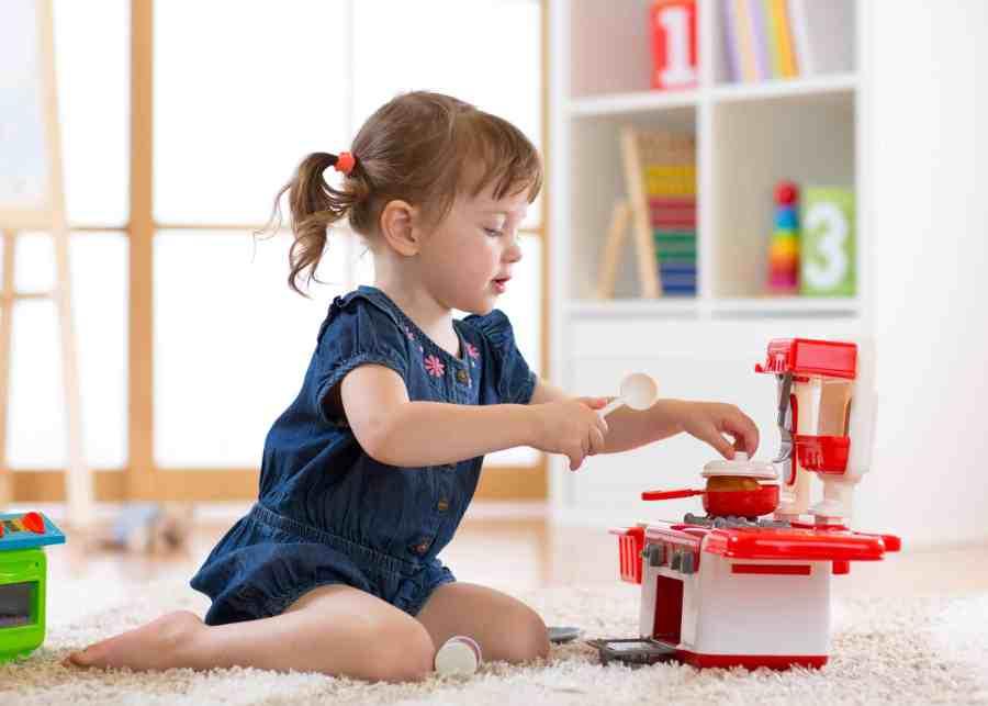 Menina brincando em cozinha de brinquedo.